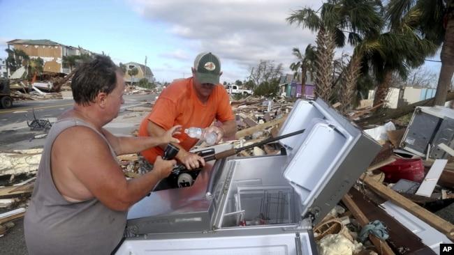 Chales Smith, izquierda, y Lee Cathey, derecha, encuentran botellas de agua en un refrigerador en medio de la US 98 en el pueblo costero de México Beach, Florida. (Douglas R. Clifford/Tampa Bay Times vía AP)