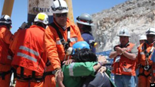 In this photo released by the Government of Chile, miner Omar Reygadas Rojas, kneeling in green, embraces his son after being rescued from the collapsed San Jose gold and copper mine, near Copiapo, Chile, Wednesday, Oct. 13, 2010.