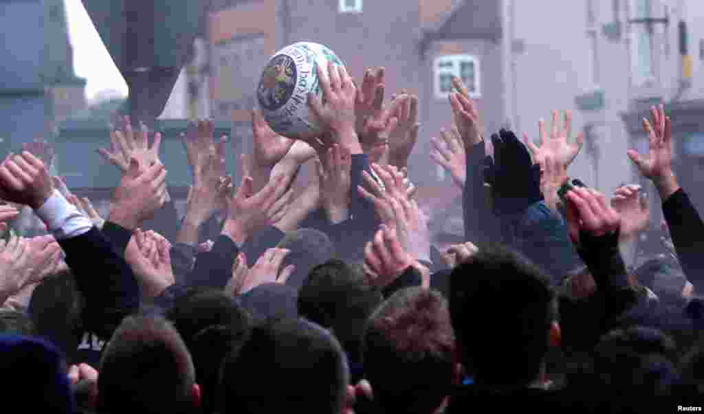 Players scrabble for the ball during the annual Ashbourne Royal Shrovetide Football match in Ashbourne, Britain.