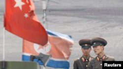 North Korean soldiers chat as they stand guard behind national flags of China (front) and North Korea on a boat anchored along the banks of Yalu River, near the North Korean town of Sinuiju, opposite the Chinese border city of Dandong, June 10, 2013.