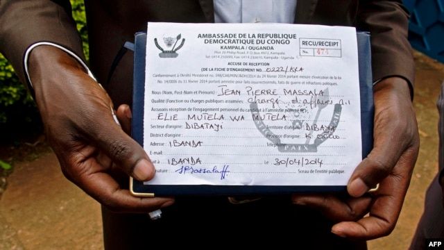 FILE - A member of the defunct M23 rebels holds an embassy form that could decide his eligibility for amnesty.