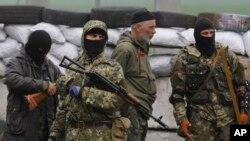 Pasukan militan bersenjata pro-Rusia berjaga di dekat barikade di wilayah Slovyansk, Ukraina (30/4). Penjabat presiden Ukraina Oleksandr Turchynov menyatakan militer negara itu dalam kondisi siaga tempur penuh menghadapi kemungkinan invasi oleh pasukan Rusia yang berkumpul perbatasan.