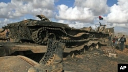 A boot belonging to a soldier loyal to Libyan leader Moammar Gaddafi on a destroyed tank after an air strike by coalition forces, along a road between Benghazi and Ajdabiyah March 21, 2011