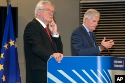 FILE - British Secretary of State for Exiting the European Union, David Davis left, and European Union chief Brexit negotiator Michel Barnier participate in a media conference at EU headquarters in Brussels, Oct. 12, 2017.