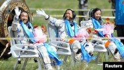 Astronot China (dari kiri) Zhang Xiaoguang, Nie Haisheng dan Wang Yaping melambaikan tangannya sesaat setelah mendarat dengan kapsul yang dibawa oleh pesawat antariksa Shenzhou-10 di wilayah Mongolia, China (26/6).