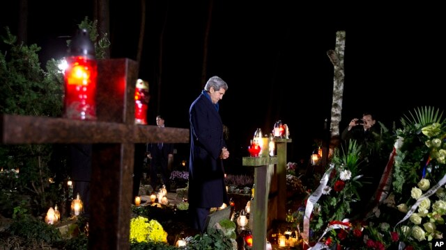 U.S. Secretary of State John Kerry pays his respects as he visits the grave of Tadeusz Mazowiecki, Poland's first democratically elected non-communist Prime Minister, in Laski, Poland, Nov. 4, 2013.