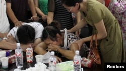 The parents (bottom) of Wang Linjia, one of the two girls killed during the Asiana Airlines plane crash on Saturday, cry at a middle school in Quzhou, Zhejiang province, July 7, 2013. An emergency vehicle rushing to the scene of the Asiana Airlines crash