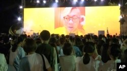"""In this image taken from video, Pavin Chachavalpongpun, administrator of the Facebook group """"Royalist Marketplace,"""" is shown delivering a pre-recorded message onscreen before a crowd attending an anti-government rally on Aug. 10, 2020, at Thammasat University in Thailand."""
