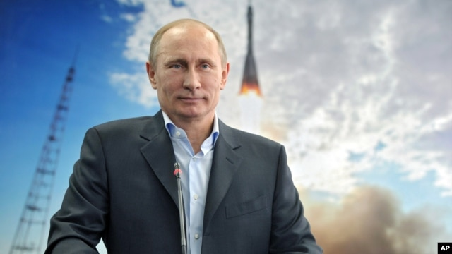 Russian President Vladimir Putin listens during a live video link with the International Space Station, April 12, 2013.