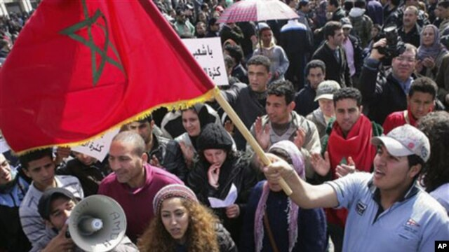 Protesters wave the Moroccan flag in Rabat, Morocco, February 20, 2011