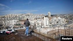 """Seorang pekerja berdiri di atas konstruksi bangunan untuk apartemen di permukiman Yahudi """"Har Homa"""" di Tepi Barat (foto: dok)."""
