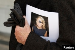 FILE - A man holds a sign honoring Sunday Times journalist Marie Colvin after a memorial service, outside St Martin in the Field in London, May 16, 2012.