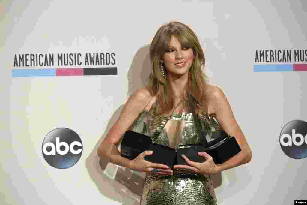 """Musician Taylor Swift poses backstage with her awards for artist of the year, favorite country artist - female, favorite country album for """"Red"""" and favorite female pop/rock at the 41st American Music Awards in Los Angeles, California, Nov. 24, 2013."""