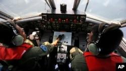 Pilot Angkatan Laut Indonesia Mayor Bambang Edi Saputro (kiri) dan Letnan Dua Tri Laksono memeriksa peta saat melakukan pencarian pesawat Boeing 777 milik Malaysia Airlines di perairan Indonesia (10/3). (AP/Binsar Bakkara)