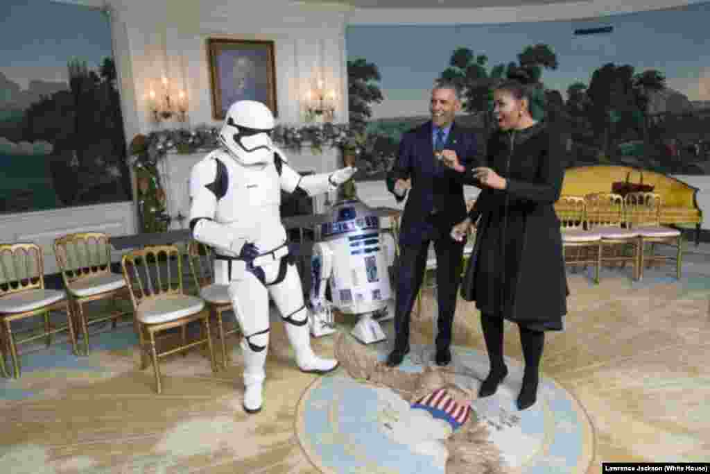President Barack Obama and first lady Michelle Obama dance with a stormtrooper and R2-D2 from Star Wars, in the Diplomatic Reception Room of the White House, Dec. 18, 2015.