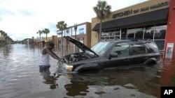 Seorang warga di Jacksonville, Florida berusaha menyelamatkan mobilnya setelah terendam banjir akibat badai Irma (11/9).