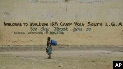 Un niño pasa frente a un cartel que da la bienvenida a refugiados que huyen de la milicia extremista Boko Haram, en Nigeria.
