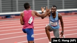 Isaiah Jewett, of the United States, and Nijel Amos, right, of Botswana, shake hands after falling in the men's 800-meter semifinal at the 2020 Summer Olympics, Sunday, Aug. 1, 2021, in Tokyo.