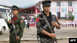 This photo taken on July 28, 2016 shows two Myanmar armed rebels from the Kachin Independence Army (KIA) securing the compound (behind) where Myanmar ethnic rebel leaders and representatives have gathered for a four-day summit in Mai Ja Yang, the KIA cont