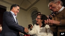 Republican presidential candidate and former Massachusetts Governor Mitt Romney greets audience members at a campaign stop in Peterborough, New Hampshire January 4, 2012, one day after winning the Iowa caucus.