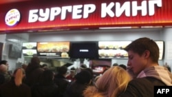 FILE - A young Russian couple waits in line on the opening day at Russia's first Burger King fast food restaurant in Moscow on January 21, 2010. (AFP PHOTO / ANDREY SMIRNOV)