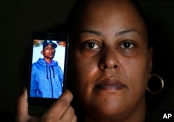 Rebecca O'Hara holds a phone showing a photo of her 25-year-old transgender son Ashton O'Hara, who was killed in July 2015, in Detroit, Nov. 11, 2015.