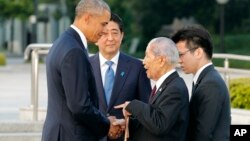 U.S. President Barack Obama, left, shakes hands and chats with Sunao Tsuboi, second right, a survivor of the 1945 atomic bombing and chairman of the Hiroshima Prefectural Confederation of A-bomb Sufferers Organization (HPCASO), as Japanese Prime Minister Shinzo Abe watches them during his visit to Hiroshima Peace Memorial Park in Hiroshima, western Japan, Friday, May 27, 2016. Obama on Friday became the first sitting U.S. president to visit the site of the world's first atomic bomb attack, bringing global attention both to survivors and to his unfulfilled vision of a world without nuclear weapons. (Kimimasa Mayama/Pool Photo via AP)