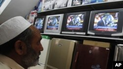 A man watches Pakistan's Prime Minister Yusuf Raza Gilani during a televised address to the parliament on the killing of Osama bin Laden, May 9, 2011