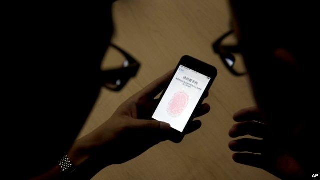 FILE - An Apple employee, right, instructs a journalist on the use of the fingerprint scanner technology built into the company's iPhone. A U.S. federal judge has ordered the company to help unlock a phone linked to a terrorist attack.