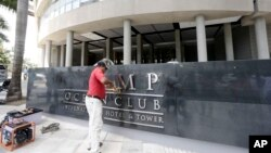 A man removes the word Trump, off a marquee outside the Trump Ocean Club International Hotel and Tower in Panama City, March 5, 2018.