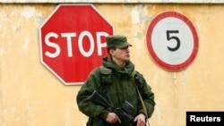 一位被认为是俄罗斯士兵的穿军服的人守卫在乌克兰在塞瓦斯托波尔的军事基地外