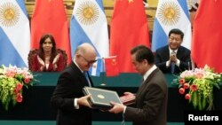 Argentinian President Cristina Fernandez de Kirchner and Chinese President Xi Jinping applaud as Argentinian Foreign Minister Hector Timerman, left, and Chinese Foreign Minister Wang Yi exchange documents Feb. 4, 2015.