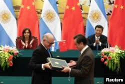 阿根廷总统克里斯蒂娜(后左)和中国国家主席习近平在人民大会堂签字仪式上。前排阿根廷外长蒂梅尔曼(左)和中国外长王毅交换文书(资料照片)