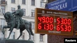 A board showing currency exchange rates, in front of a monument to Prince Yury Dolgoruky, who founded Moscow in 1147, in the capital Moscow, Dec. 1, 2014.