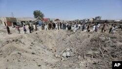 Des Afghans regardent un cratère causé par le bombardement d'un camion, à Kaboul, en Afghanistan, lundi 1 août 2016. (AP Photos/Rahmat Gul)