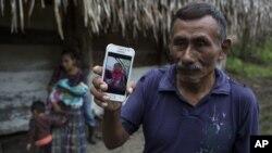 Domingo Caal Chub, de 61 años, muestra una fotografía de su nieta, Jakelin Amei Rosmery Caal Maquín, en Raxruhá, Guatemala.