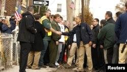 美國總統奧巴馬視察了紐約遭受桑迪颶風重創的一些地區﹐和一名史丹頓島的居民握手
