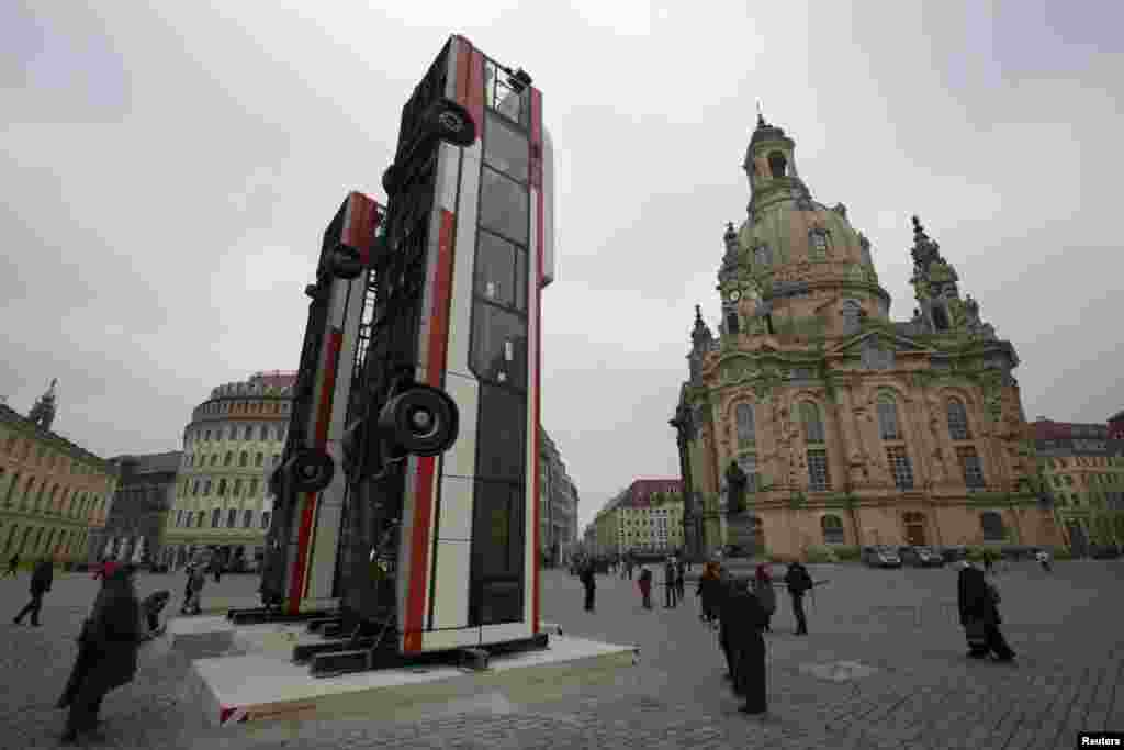 "People walk next to the art installation ""Monument"" by Syrian artist Manaf Halbouni, made from three passenger busses in Dresden, Germany."