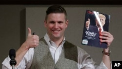 FILE - Richard Spencer, who leads a movement that mixes racism, white nationalism and populism, holds up a magazine cover showing President-elect Donald Trump before signing it for a supporter in College Station, Texas, Dec. 6, 2016.
