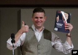 FILE - Richard Spencer, who leads a movement that mixes racism, white nationalism and populism, holds up a magazine cover showing then-President-elect Donald Trump before signing it for a supporter, Dec. 6, 2016, in College Station, Texas.