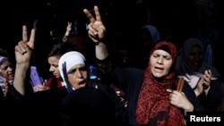 "Muslimah Palestina mengacungkan tanda ""V"" (kemenangan) setelah Israel setuju untuk membongkar perangkat keamanan dari komplek masjid Al-Aqsa di kota tua Yerusalem, Kamis (27/7)."