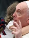 A child hugs Pope Francis during the weekly general audience in the Paul VI Audience Hall at the Vatican.