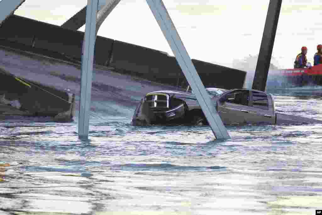 A damaged truck sits in the water on a portion of the Interstate-5 bridge that is submerged after it collapsed into the Skagit river dumping vehicles and people into the water in Mount Vernon, Wash., May 23, 2013.