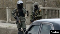 FILE - Pro-Russia armed men stand at an improvised checkpoint in Slovyansk, eastern Ukraine, April 12, 2014.