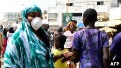 Une pèlerine de la confrérie mouride, un ordre soufi, portant un masque, arrive à la Grande Mosquée de Touba, avant la fête religieuse du Magal commémorant l'exil de son fondateur, le grand marabout Sheikh Amadou Baba, le marabout, Touba, Sénégal, 27 octo