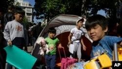 Anak-anak pengungsi membawa mainan dan tas di Lapangan Victoria di Athena, Yunani (1/10).