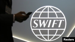FILE - A man using a cellphone passes the logo of global secure financial messaging services cooperative SWIFT, Toronto, Canada.
