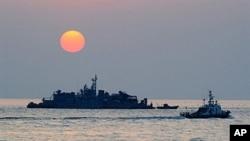 一艘南韓政府的船隻在延坪島附近海域上的南韓軍艦旁邊經過