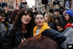 Actresses Asia Argento, left, and Rose McGowan pose during a demonstration to mark International Women's Day in Rome, March 8, 2018. Asia Argento, an Italian actress who helped launch the #MeToo movement, is launching a new movement, #WeToo, which aims to unite women against the power imbalance in favor of men.