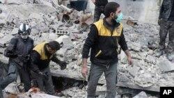 Esta foto divulgada el martes, 13 de marzo de 2018, por el grupo de defensa civil sirio Cascos Blancos, muestra a miembros del grupo removiendo un cadáver después de un ataque aéreo en un suburbio de Damasco, Siria.